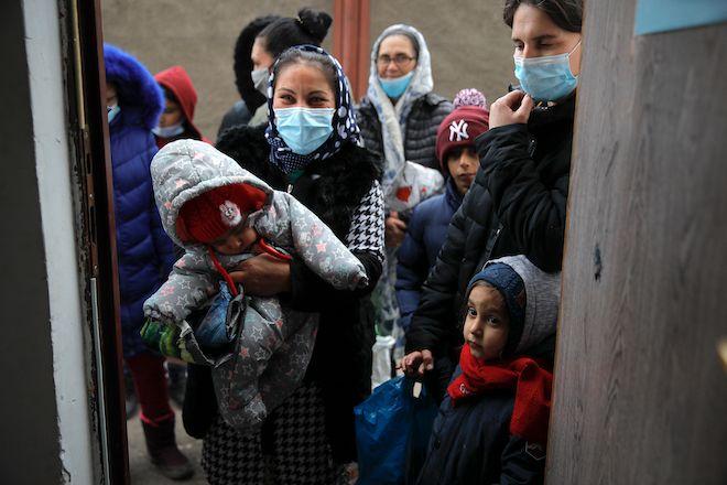Άνθρωποι περιμένουν δωρεά φαγητού για το χριστουγεννιάτικο δείπνο τους στο Βουκουρέστι της Ρουμανίας, 24 Δεκεμβρίου 2020.