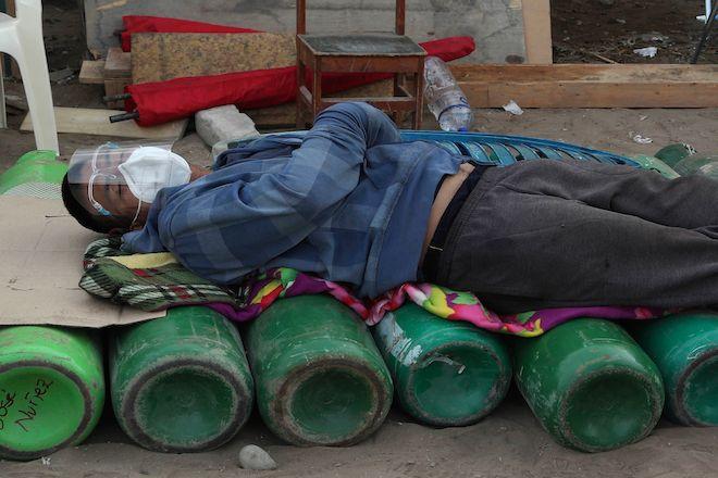 Άντρας κοιμάται πάνω σε άδειους κυλίνδρους οξυγόνου περιμένοντας να ξαναγεμίσει τη δεξαμενή του, καθώς η έλλειψη ιατρικού οξυγόνου εξακολουθεί να είναι ο κανόνας στο Περού, 18 Φεβρουαρίου 2021